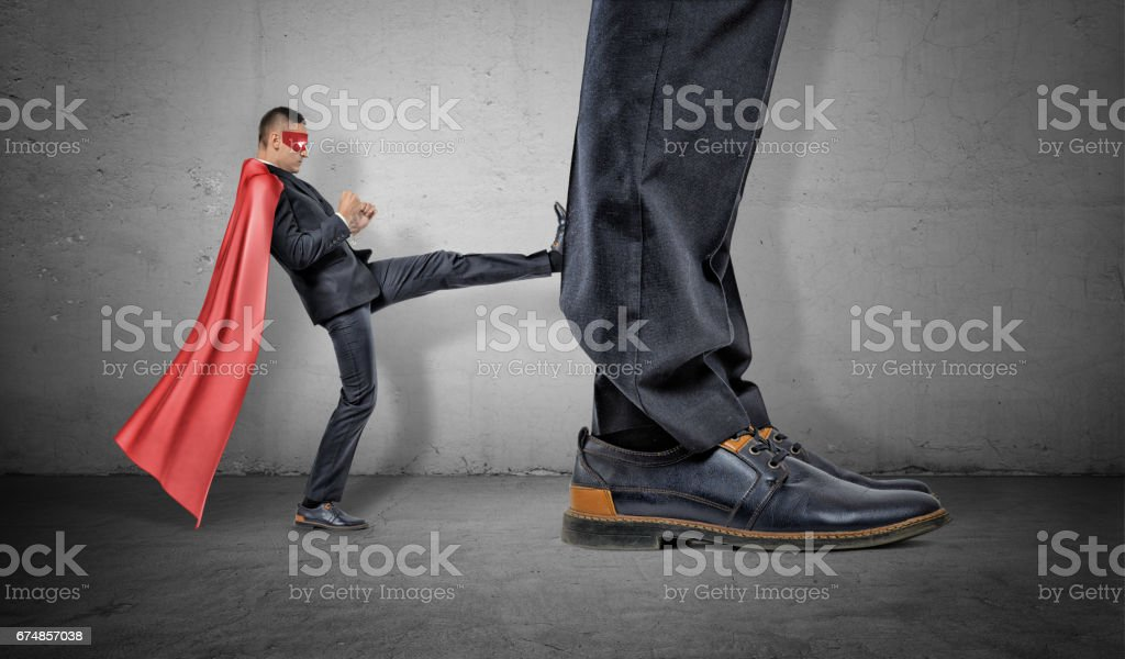A tiny businessman in a red cape and an eyemask kicking at a retreating giant foot stock photo