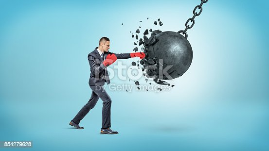 istock A tiny businessman in red boxing gloves breaks a large swinging wrecking ball in small pieces. 854279628