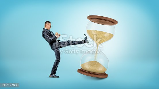 A tiny businessman kicks and shakes a large hourglass with half of its sand already in the lower chamber. Harness your time. Efficient workhours. Fight against time.