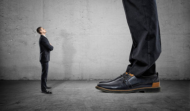 Tiny businessman looking up on huge legs of another man - foto de stock
