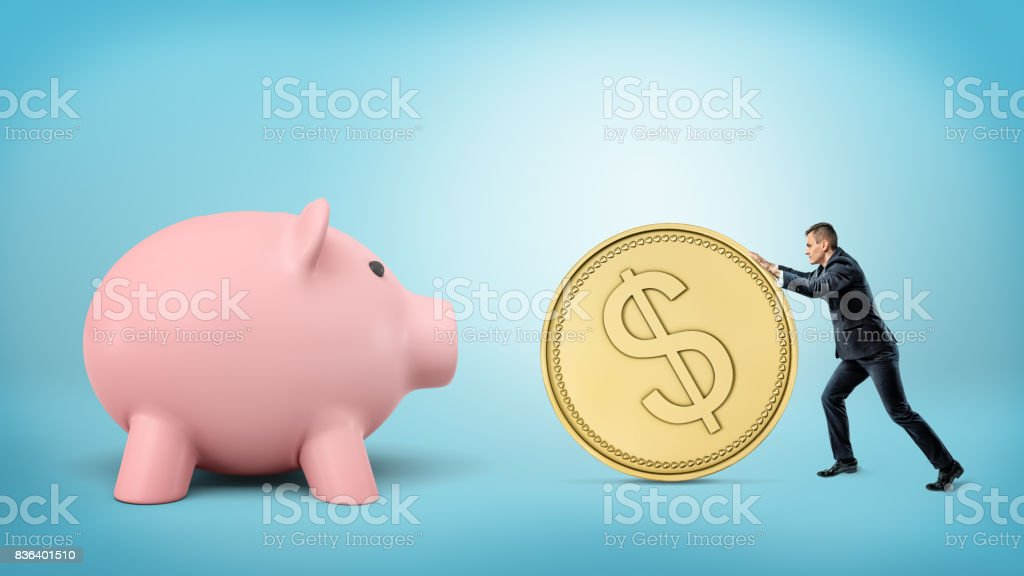 A tiny businessman rolls a huge golden dollar coin in the direction of a giant piggy bank stock photo