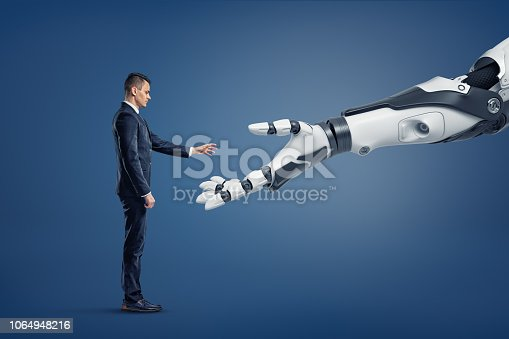 istock A tiny businessman stands in a side view and lifts his hand to touch a giant robotic arm. 1064948216