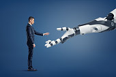 A tiny businessman stands in a side view and lifts his hand to touch a giant robotic arm.