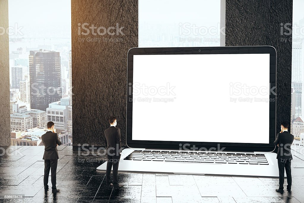 Tiny businessmen looking at blank laptop stock photo