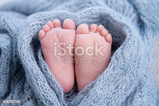 Little toes, baby feet wrapped in a heart blanket