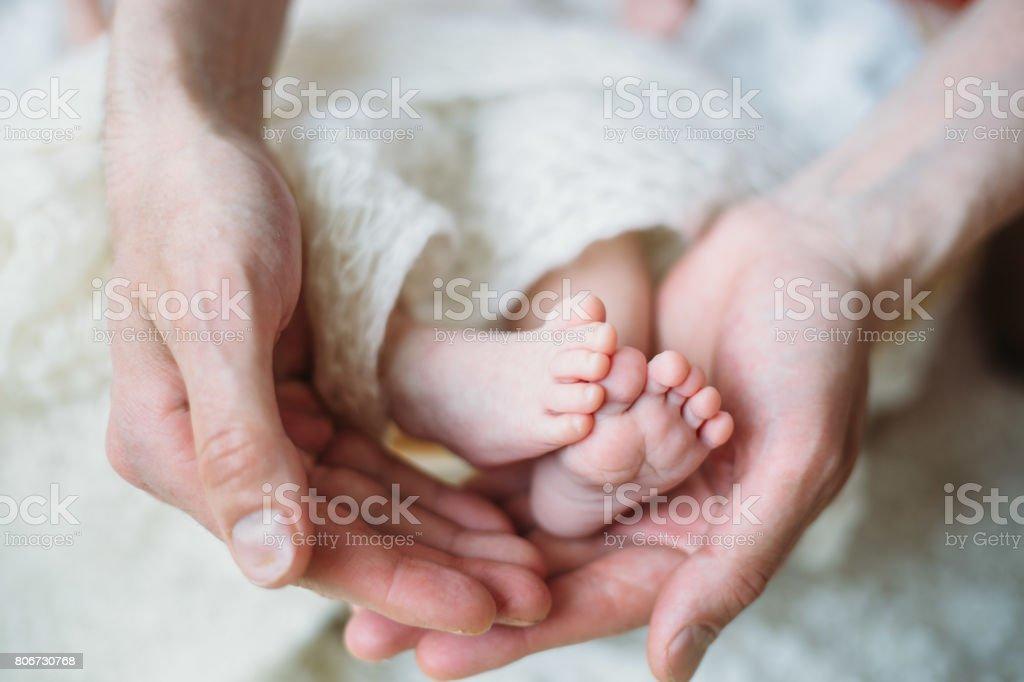 Tiny foot of newborn baby stock photo