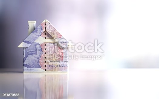 Tiny house model textured with twenty British pound banknotes on reflective surface. Horizontal composition with copy space and selective focus. Great use for real estate marketing concepts.