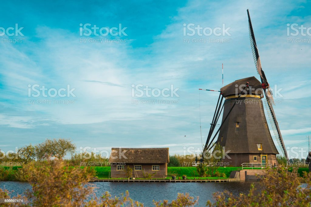 tiny house with wind mill, Unesco, in water landscape Kinderdijk, The Netherlands, against blue sky stock photo