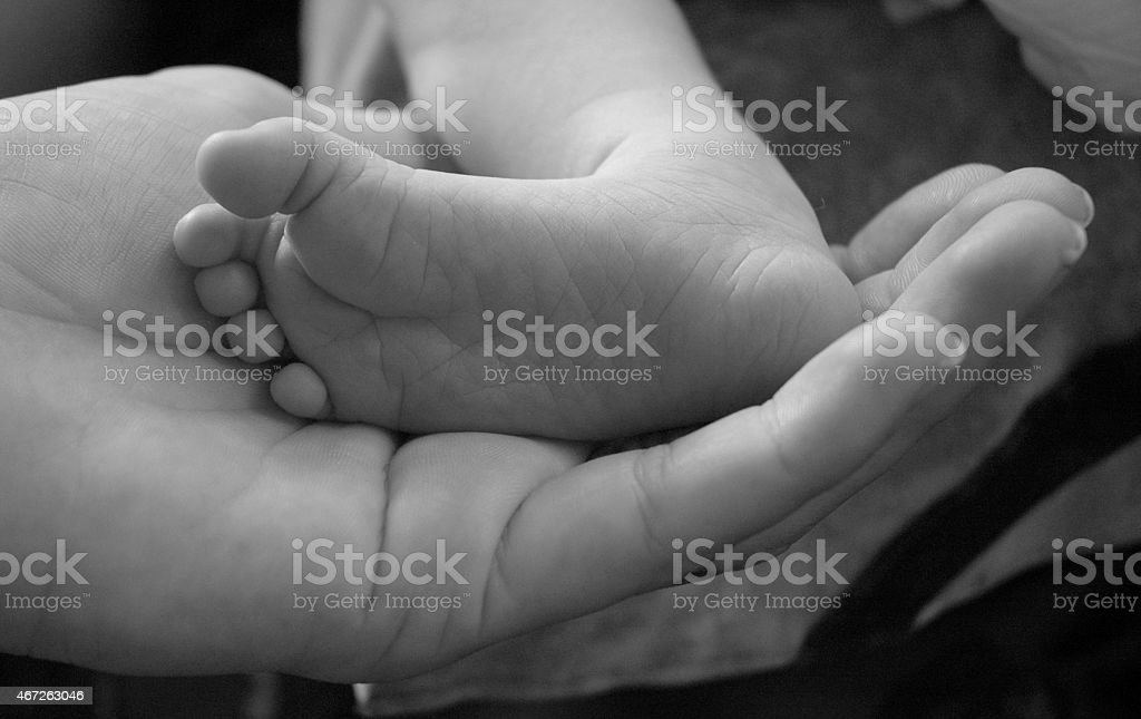 Tiny Infant Foot in mother's hand black and white stock photo