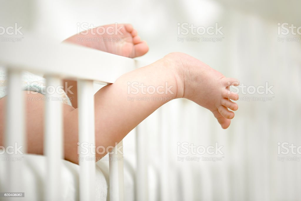 Tiny legs caught between the crib frame stock photo