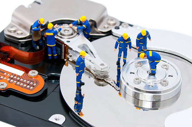 Tiny little workers working on a computer hard disk stock photo