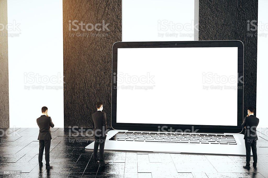 Tiny men looking at blank laptop stock photo