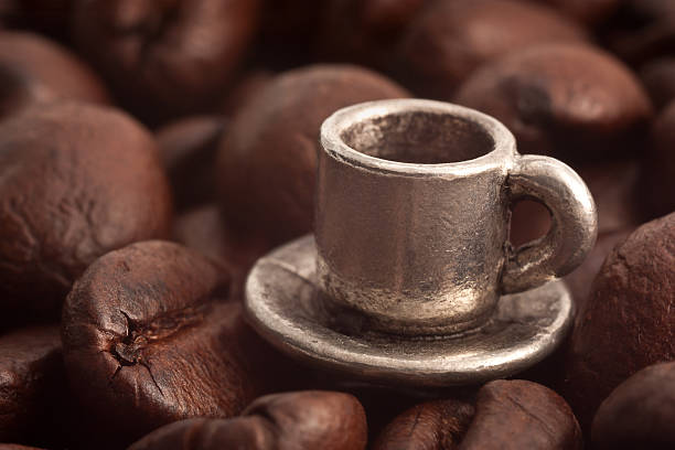 Tiny Metal Cup and Saucer with Coffee Beans stock photo