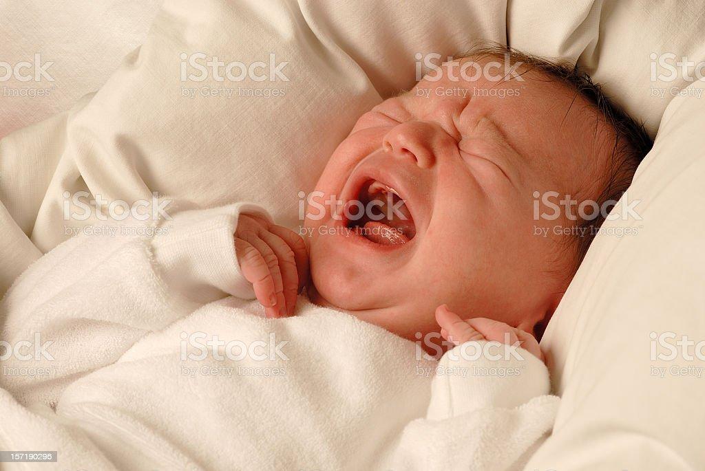 A tiny new born child crying sadly stock photo