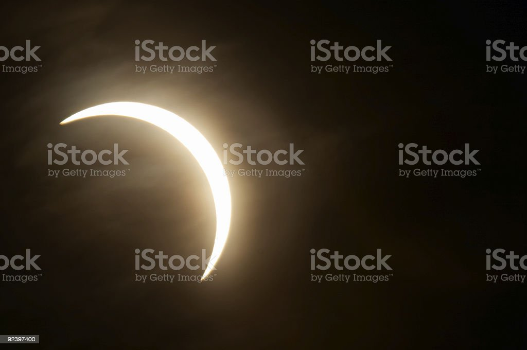 Tiny piece of moon peeking out from behind eclipse in black stock photo