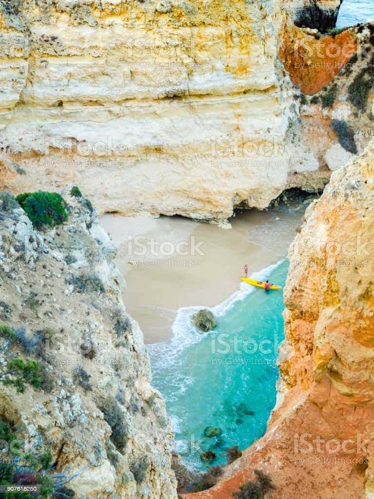 Tiny remote beach in Lagos, Algarve, Portugal. A hidden secret beach between limestone walls. People with a yellow kayak visiting the beach. stock photo