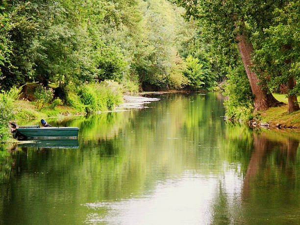 Tiny rowboat docked on the bank of a tranquil river stock photo