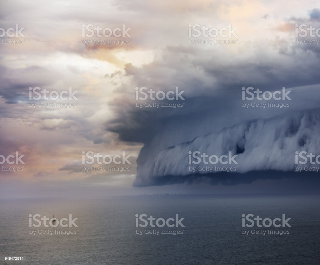 Tiny sailing boat and incoming storm - foto stock