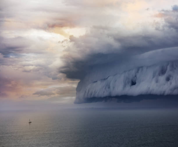 tiny sailing boat and incoming storm - storm stock photos and pictures