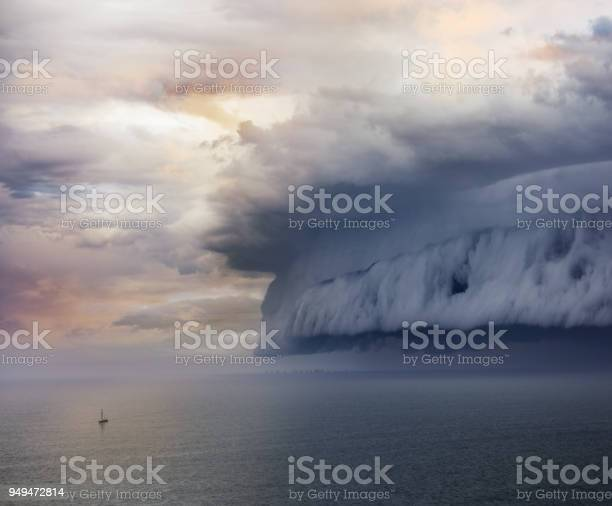 Photo of Tiny sailing boat and incoming storm