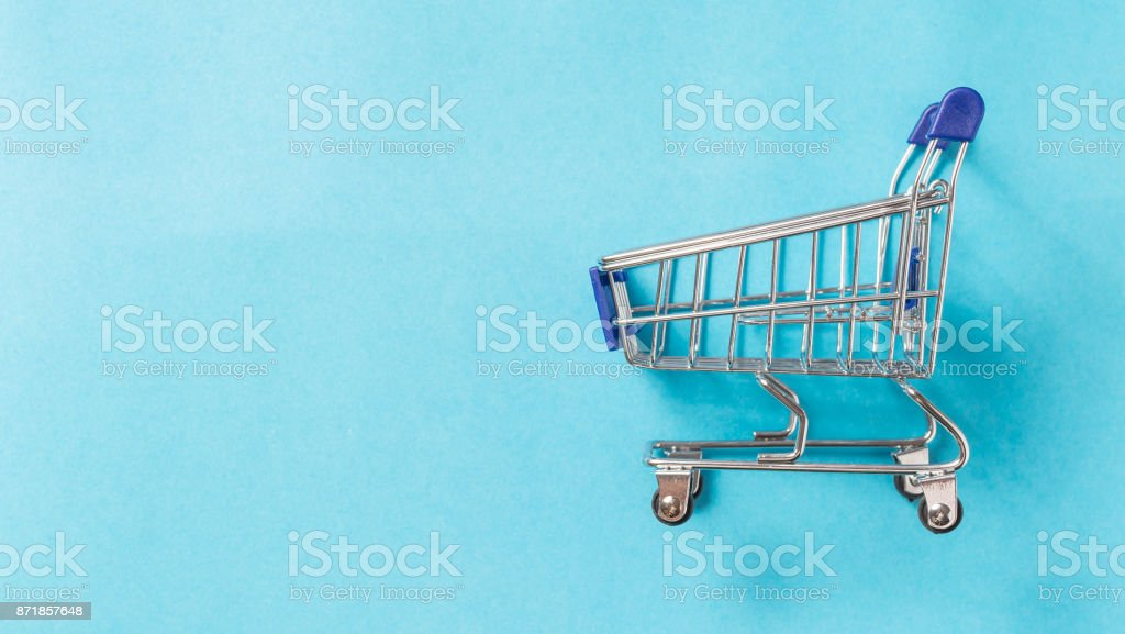 Tiny shopping cart on the blue background with space for text stock photo