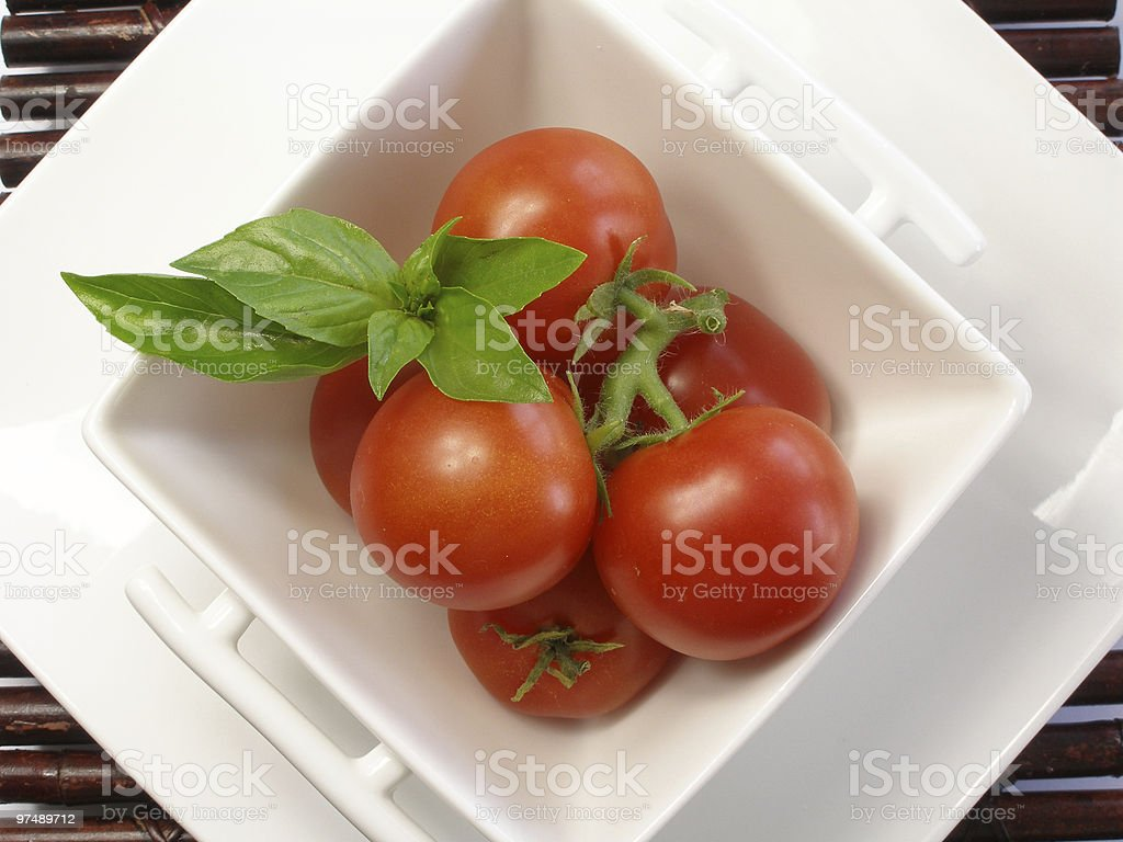 Tiny tomatoes in a square bowl with basil royalty-free stock photo