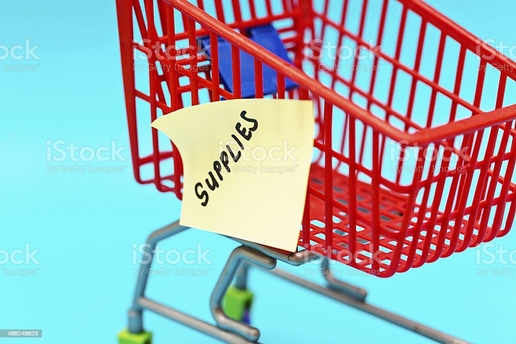 Tiny trolley with label saying Supplies: time to shop! royalty-free stock photo