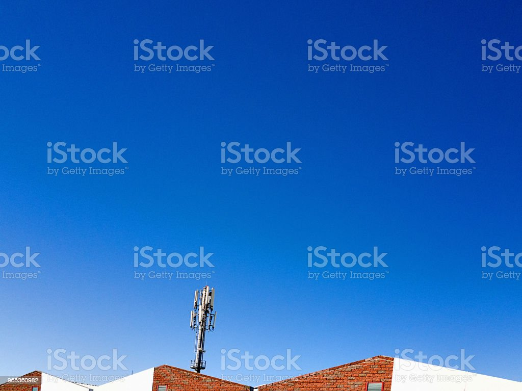 Tip of a mobile phone bases station over buildings royalty-free stock photo