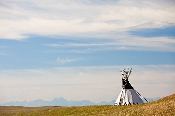 Tipi on the Great Plains A teepee on the prairie. Horizontal image. Colour. First Nations culture. Teepee is also tipi. Aboriginal culture and historic attractions are popular on the great plains, which has a rich history of many tribes and peoples who were here long before white people settled these vast areas. This tipi is located in southern Alberta near the Head-Smashed-In Buffalo Jump, a major tourist attraction and museum in Alberta, Canada.  alberta stock pictures, royalty-free photos & images