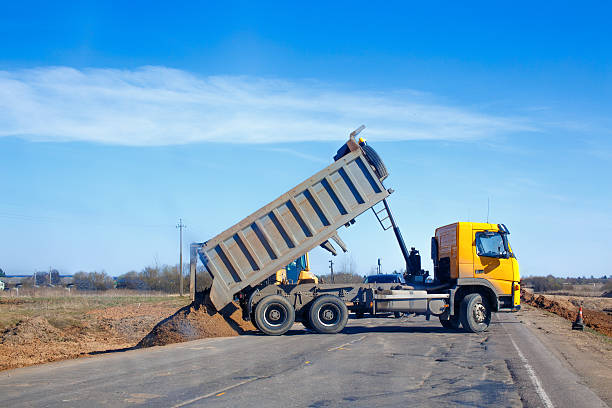 tipper unloads sand on the road stock photo