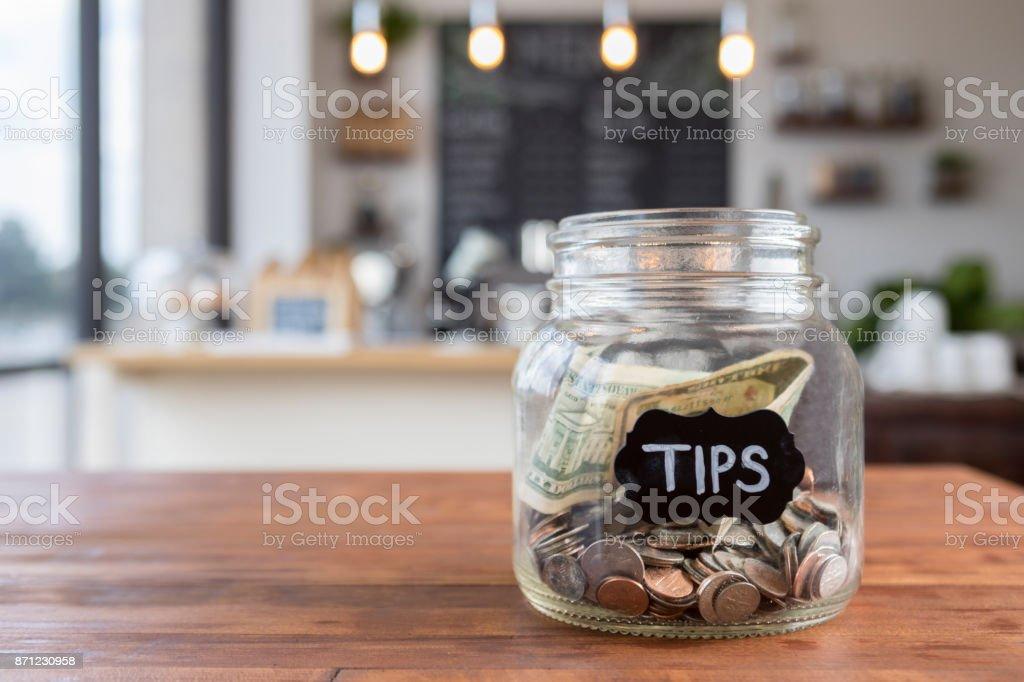 ''Tips'' jar on coffee shop table stock photo