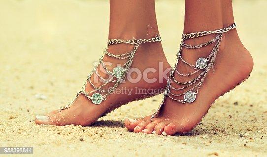 694409862 istock photo Tiptoed woman's feet on the tropical sand. 958398844