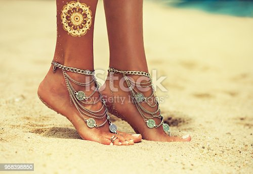 694409862 istock photo Tiptoed woman's feet on the tropical sand. 958398850
