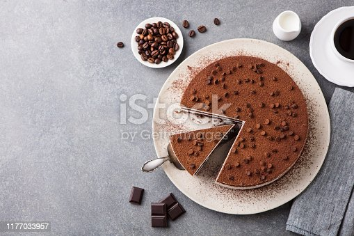 Tiramisu cake with chocolate decoration on a plate. Grey stone background. Top view. Copy space