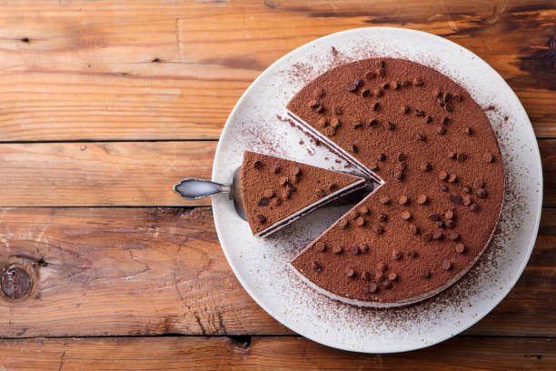 Tiramisu cake with chocolate decoration on a plate. Wooden background. Copy space. Top view. stock photo