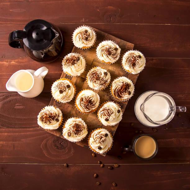 tiramisu-cupcakes mit kakao und kaffeekörner auf einem holzbrett neben krüge aus milch, sahne und einer tasse kaffee verziert. ansicht von oben flach legen - heiße schokoladen cupcakes stock-fotos und bilder