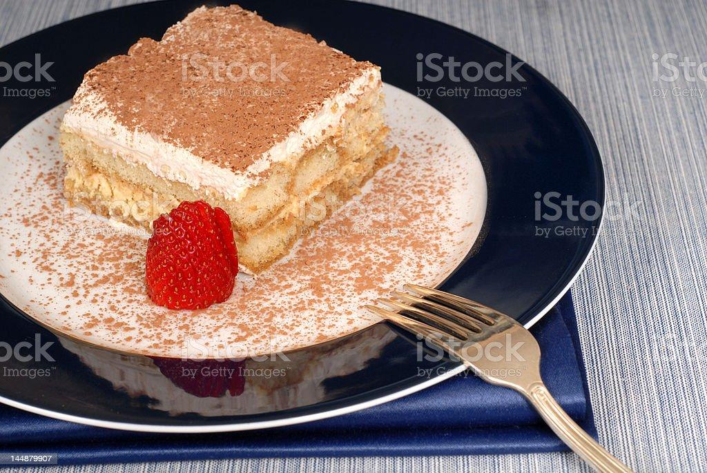 Tiramisu dusted with cocoa on a blue plate