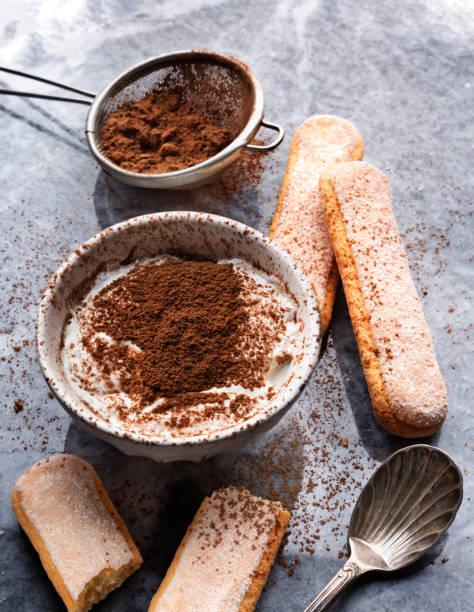 tiramisú ingredientes (crema de dedos, cacao, señora) sobre un fondo de mármol. comida casera y dulce - tiramisu fotografías e imágenes de stock