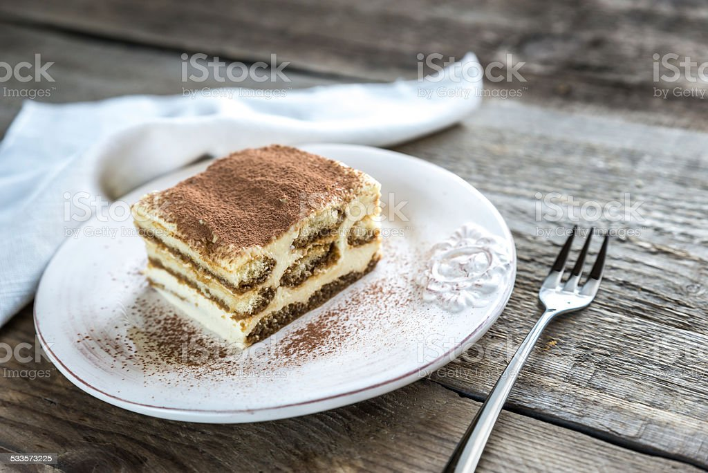 Tiramisu on the plate on the wooden background stock photo