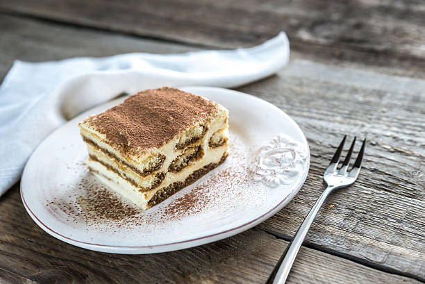 Tiramisu on the plate on the wooden background Tiramisu on the plate on the wooden background tiramisu stock pictures, royalty-free photos & images