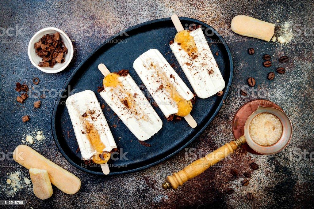Tiramisu popsicles. Ice pops with italian savoiardi cookies and tiramisu ingredients on rustic kitchen table. Top view, overhead, flat lay stock photo
