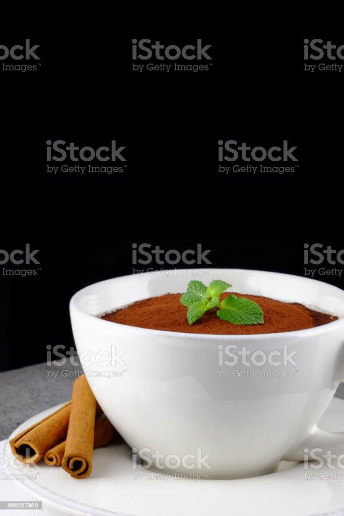 Tiramisu, traditional italian dessert in a large white cup decorated...
