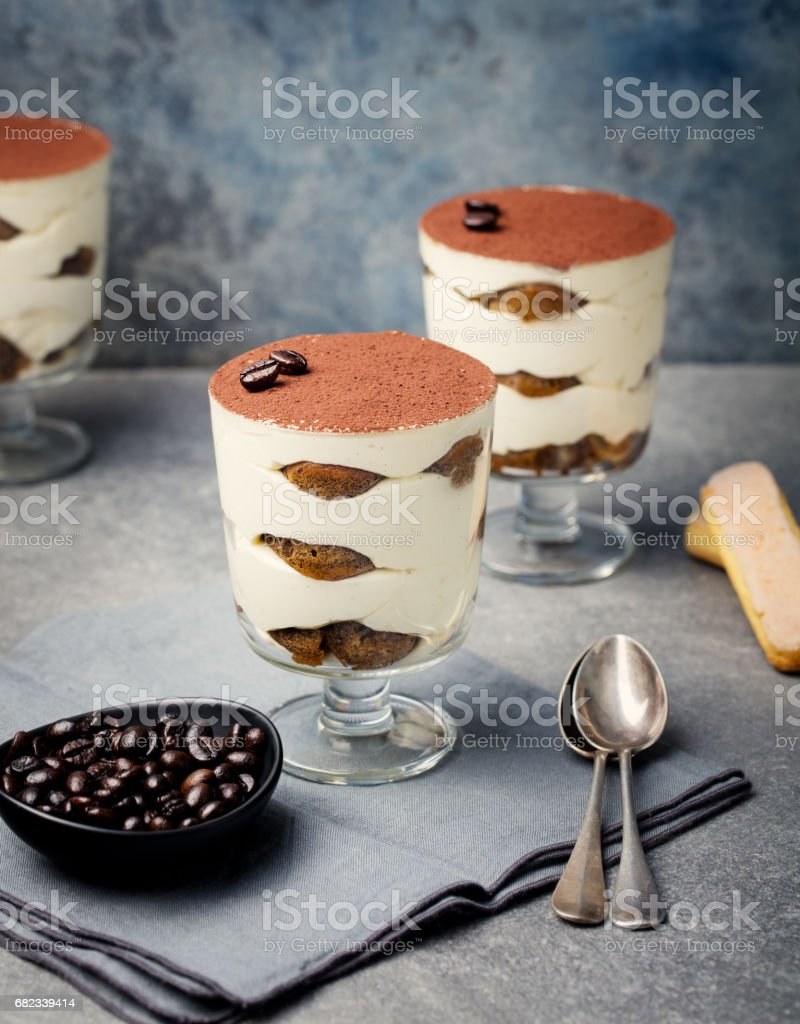 Tiramisu, traditional Italian dessert in glass on a grey stone background. foto stock royalty-free