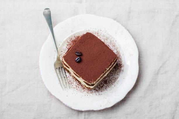 tiramisu, traditionelle italienische dessert auf einem weißen teller. kopieren sie raum. ansicht von oben. - tiramisu stock-fotos und bilder