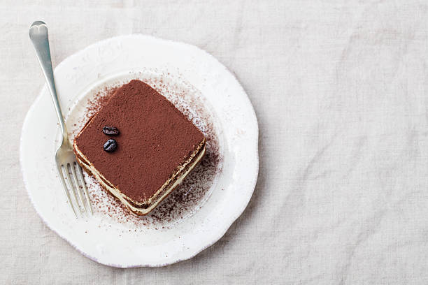 Tiramisu, traditional Italian dessert on a white plate Top view Tiramisu, traditional Italian dessert on a white plate Top view Copy space tiramisu stock pictures, royalty-free photos & images