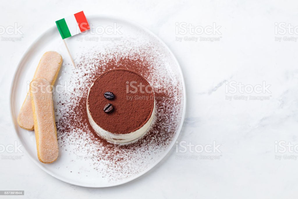 Tiramisu, traditional Italian dessert on white plate with Italian flag stock photo