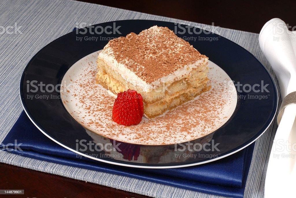 Tiramisu with sliced strawberry on a blue plate