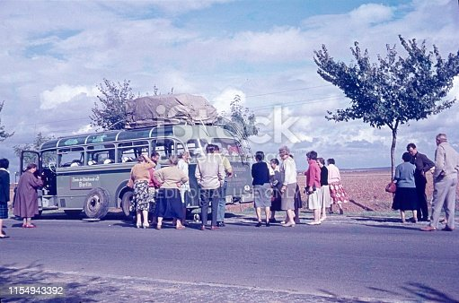 Castilla-La Mancha, Spain, 1959. Tire breakdown of a tourist bus on a spanish country road. Furthermore: Passengers (tourists).