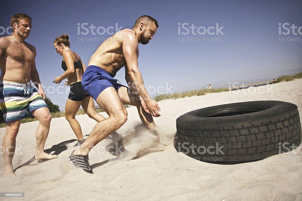 Tire flip gym exercise on beach royalty-free stock photo