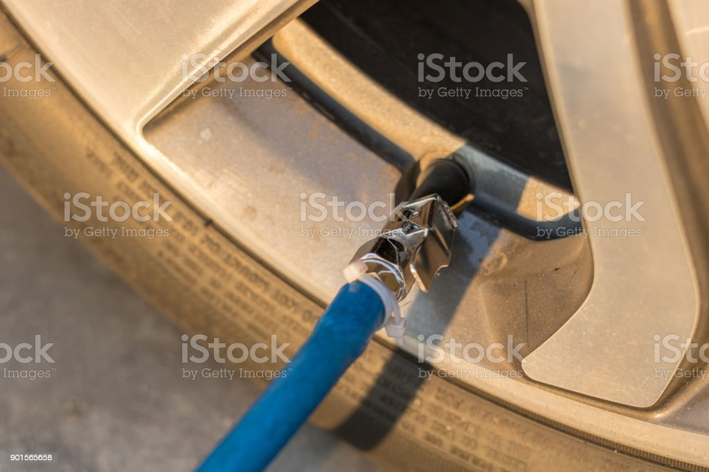 Tire inflation. Filling air into a car tire. stock photo